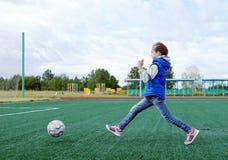 Mała dziewczynka bawić się piłkę nożną na boisko do piłki nożnej obraz royalty free