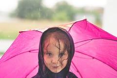 Mała dziewczynka bawić się samotnego outside w złej pogodzie Obraz Royalty Free