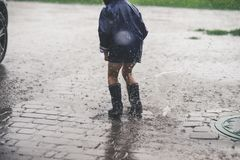 Mała dziewczynka bawić się samotnego outside w złej pogodzie Fotografia Stock