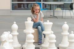 Mała dziewczynka bawić się szachową grę Zdjęcia Royalty Free