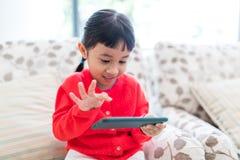 Mała dziewczynka bawić się telefon komórkowego w domu fotografia royalty free