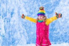 Mała dziewczynka bawić się w śnieżnym parku Zdjęcie Royalty Free