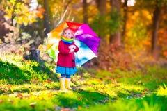 Mała dziewczynka bawić się w deszczu w jesieni Zdjęcie Royalty Free