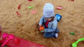 Mała dziewczynka bawić się w piaskownicie zdjęcie wideo