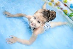 Mała dziewczynka bawić się wodę w pływackim basenie i rozpyla fotografia stock