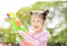 mała dziewczynka bawić się wodnych pistolety zdjęcia stock