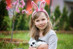 Mała dziewczynka bawić się z białym królikiem w parku na pogodnym lecie fotografia royalty free