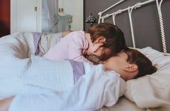 Mała dziewczynka bawić się z chłopiec nad łóżkiem obraz royalty free