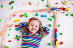 Mała dziewczynka bawić się z drewnianymi pociągami Zdjęcie Stock