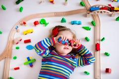 Mała dziewczynka bawić się z drewnianymi pociągami Obraz Royalty Free