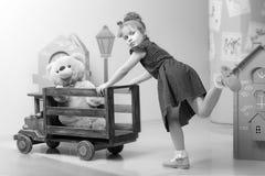 Mała dziewczynka bawić się z dużym drewnianym samochodem Zdjęcie Royalty Free