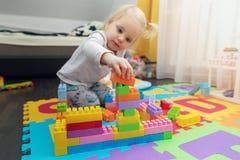 Mała dziewczynka bawić się z elementami na podłodze obraz royalty free