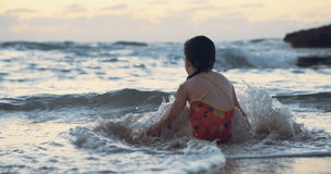 Mała dziewczynka bawić się z fala przy plażą podczas zmierzchu zbiory wideo