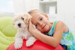 Mała dziewczynka bawić się z jej małym puszystym psem Zdjęcia Stock