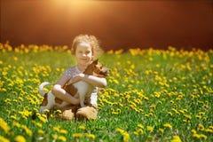 Mała dziewczynka bawić się z jej szczeniakiem Zdjęcia Stock