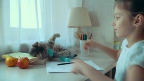 Mała dziewczynka bawić się z jej zwierzę domowe kotem podczas gdy robić pracie domowej zdjęcie wideo