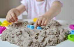 Mała dziewczynka bawić się z kinetycznym piaskiem w domu fotografia royalty free