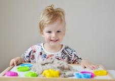 Mała dziewczynka bawić się z kinetycznym piaskiem w domu obrazy stock