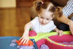 Mała dziewczynka bawić się z kinetycznym piaskiem w domu, gry, edukacja, dzieci obrazy royalty free