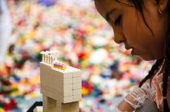 Mała dziewczynka bawić się z kolorowymi cegłami lub dziecinem w domu obrazy stock
