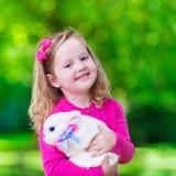 Mała dziewczynka bawić się z królikiem Fotografia Stock