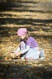Mała dziewczynka bawić się z liśćmi Obrazy Stock