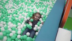 Mała dziewczynka bawić się z małymi piłkami na boisku w dzieciach centrum zbiory wideo