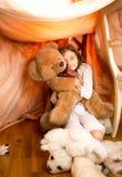 Mała dziewczynka bawić się z misiem w zawdzięczający sobie domu Zdjęcie Stock