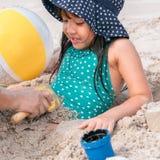Mała dziewczynka bawić się z piaskiem przy tropikalną plażą w sumie zdjęcie royalty free