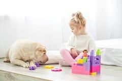 Mała dziewczynka bawić się z psem w pokoju Pojęcie życie zdjęcie stock