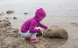 Mała dziewczynka bawić się z skałami Obrazy Royalty Free
