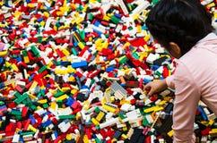 Mała dziewczynka bawić się z wiele plastikowymi budynek cegłami rozdziela zdjęcie stock