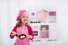 Mała dziewczynka bawić się z zabawkarską kuchnią zdjęcia stock