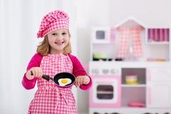 Mała dziewczynka bawić się z zabawkarską kuchnią obraz stock