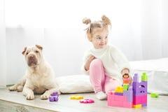 Mała dziewczynka bawić się zabawki Dziecko w puloweru i menchii spodniach Th obrazy royalty free