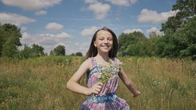 Mała dziewczynka bieg na łące z z bukietem kwiaty zdjęcie wideo