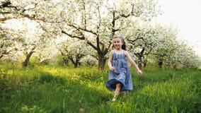 Mała dziewczynka bieg przez kwiecenie ogródu zdjęcie wideo