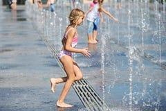 Mała dziewczynka bieg wśród fontann Zdjęcie Stock
