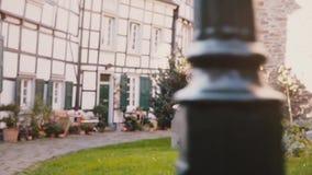 Mała dziewczynka bieg w pięknym tajemniczym starym miasteczku Tylny widoku zwolnione tempo Brukująca ulica, przyrodni szalunków d zdjęcie wideo