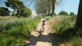 Mała dziewczynka bieg wzdłuż ścieżka śladu w naturze zdjęcie wideo