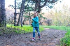 Mała dziewczynka bieg wzdłuż lasowej ścieżki, jaskrawa fotografia wiosna Zdjęcia Stock