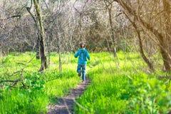 Mała dziewczynka bieg wzdłuż lasowej ścieżki, jaskrawa fotografia wiosna Obrazy Royalty Free