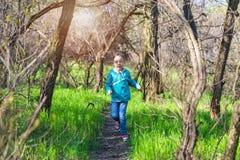 Mała dziewczynka bieg wzdłuż lasowej ścieżki, jaskrawa fotografia wiosna Fotografia Royalty Free