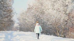 Mała dziewczynka biega na śnieżnej drodze zdjęcie wideo