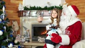 Mała dziewczynka bierze selfie z Santa i jej teraźniejszością, dziecko wizyty Santa Claus siedziba, boże narodzenia zbiory