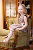 Mała dziewczynka blondyn jest ubranym korony pozycję przy krzesłem Zdjęcie Stock