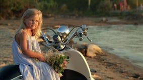 Mała dziewczynka blondynka siedzi z różowym kwiatem w rękach na białym moped na piasku morzem zbiory