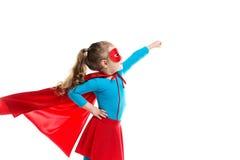 Mała dziewczynka bohater w pelerynie odizolowywających na białym tle czerwonej masce i fotografia royalty free