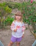 Mała dziewczynka chodzi kwiatu w jej rękach i trzyma, outdoors obraz stock
