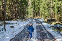 Mała dziewczynka chodzi przez śnieżnego lasu Zdjęcia Royalty Free